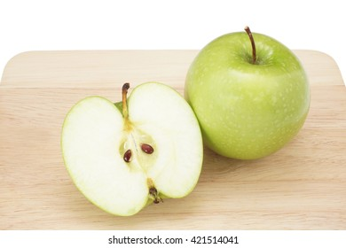 whole green apple and half with leaf isolated on wood background