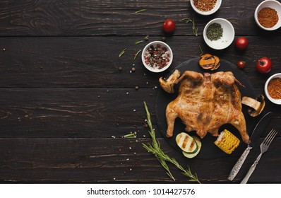 Whole grilled chicken with crispy golden crust skin served with barbecued zucchini, carrot, corn, cutlery and spices assortment on dark table, top view, copy space