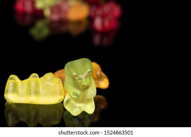 Lot of whole gummy bear front focus isolated on black glass
