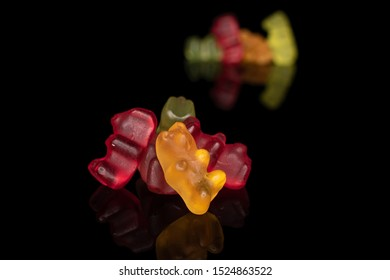 Lot of whole gummy bear isolated on black glass