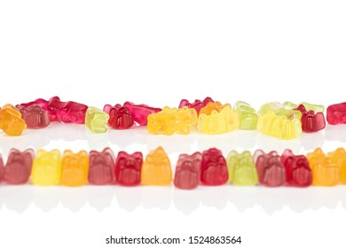 Lot of whole gummy bear in row isolated on white background
