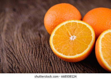 whole and half cut navel orange on wooden background