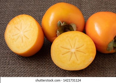Whole and half of fresh ripe persimmons. Japanese persimmon (Diospyros kaki)