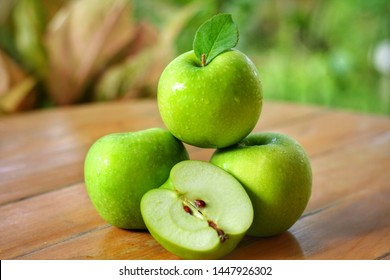 Whole and half of Green Apple(Malus pumila) on wooden table with blurred garden background.Sweet,sour and freshness taste.Have a lot of fiber, vitamins and minerals.Food,Fruits or healthcare concept.
