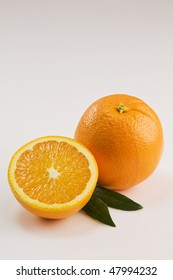 A Whole and a Half Orange Isolated on White with Leaves Vertical