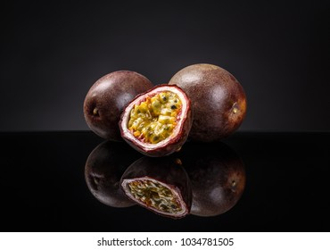 Whole and half passion fruits (maracuya) on clipping path black background