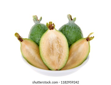 Whole, half and quarter slices of fresh pineapple guava fruit in a small white bowl isolated on white background.