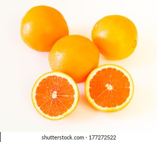 Whole and halved  the cara cara oranges with its pinkish red color interior, on light background