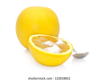 whole and halved grapefruit with a spoonful of sugar on it