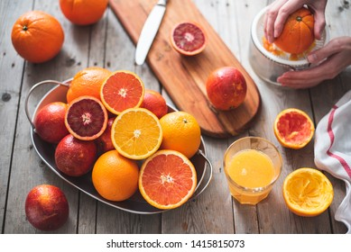 Whole and halved a variety of oranges on a metal tray, orange juice in a glass and juicer on a gray wooden table
