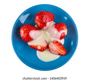 Whole and halves of strawberries with condensed milk in blue saucer isolated on white background. Top view