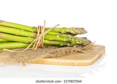 Lot of whole healthy green asparagus on bamboo cutting board with straw rope and jute fabric isolated on white background