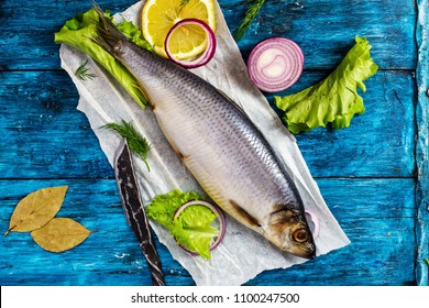 Whole herring on rustic deep blue wooden background, top view