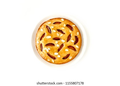 Whole homemade plum cake, glazed with victoria plum jam and decorated with roasted almond slivers, isolated on white background.