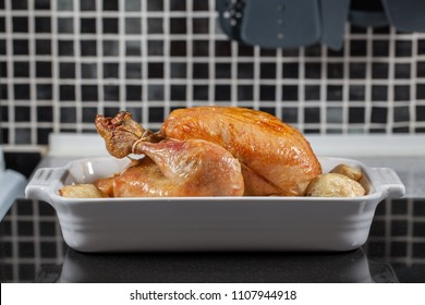 Whole hot oven cooked roast chicken. Prepared sunday meal with potatoes on the kitchen worktop ready for carving and serving for dinner.