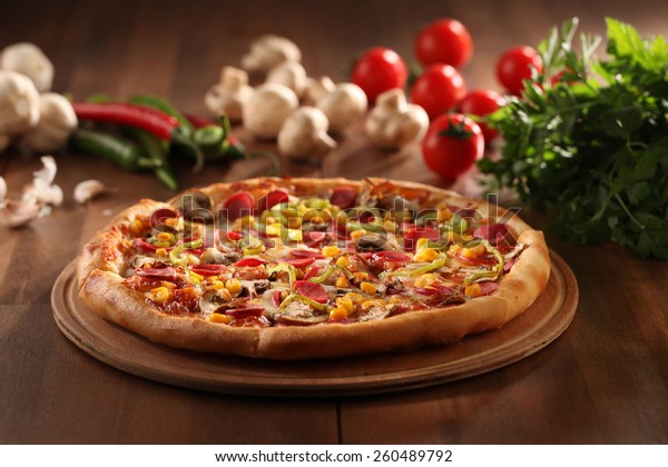 whole italian pizza on wood table with ingredients