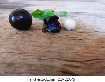A whole jabuticaba a shell of jabuticaba a lump and a leaf on rustic wooden table