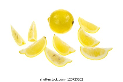 A whole lemon in the background with several wedges in the foreground on a white background.