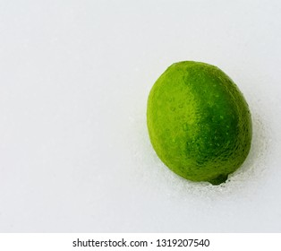 Whole lime covered in water drops on icy white background