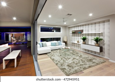 Whole living illuminated with small light under the ceiling, there is a fan middle of the roof. The room has wooden floors with wool carpet on it. There are white sofas with pillows and wall shelves