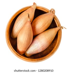 Whole long shallots in wooden bowl.