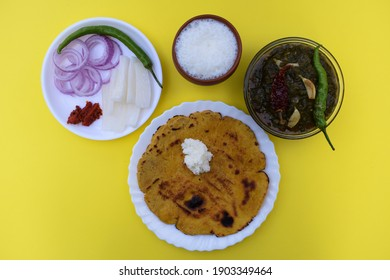 Whole meal of North Indian Makki roti and sarson saag with onion chilly salad, pickle and sweet lassi in an authentic way with white butter and green chilly. Classic punjabi dish.