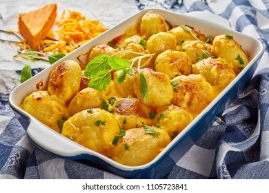 whole new potatoes baked with cheddar cheese butter sauce in a baking dish on a white wooden table with grated cheddar cheese and kitchen towel at the background, view from above, close-up