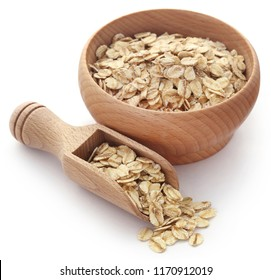 Whole oats in wooden bowl isolated over white background