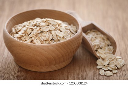 Whole oats in wooden scoop and bowl on natural surface