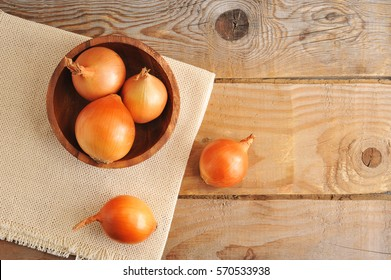 whole onion bulbs in a wooden plate on wooden background in rustic style