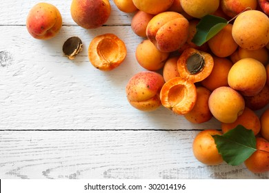 Whole orange apricots with red blush, from above, space for text. Open apricot with stone and leaves. On rustic white wood.