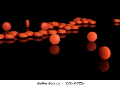 Lot of whole orange tablet pharmacy front focus isolated on black glass