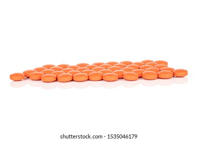 Lot of whole orange tablet pharmacy heap isolated on white background