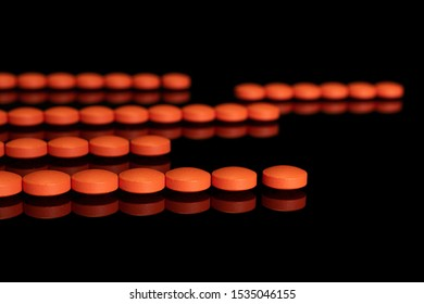 Lot of whole orange tablet pharmacy in row isolated on black glass