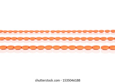 Lot of whole orange tablet pharmacy in row isolated on white background