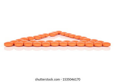 Lot of whole orange tablet pharmacy triangle isolated on white background