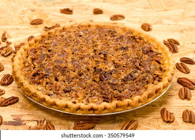 Whole pecan pie with pecans on wooden background.