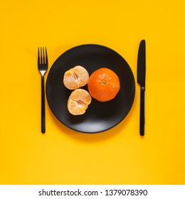 Whole and peeled tangerines in black plate on bright yellow background. Top view point.