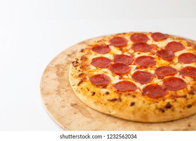 Whole pepperoni pizza on a stone with a white background