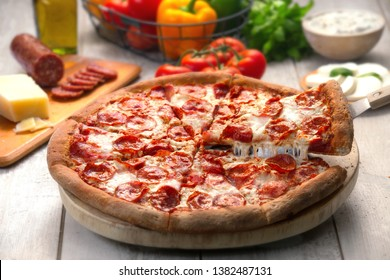 Whole pepperoni pizza pie with a lifted slice of stringy cheesy, on wooden table with ingredients
