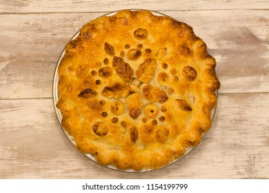 A whole pie with a decorative top crust featuring leaf and berry designs on a wooden table backdrop