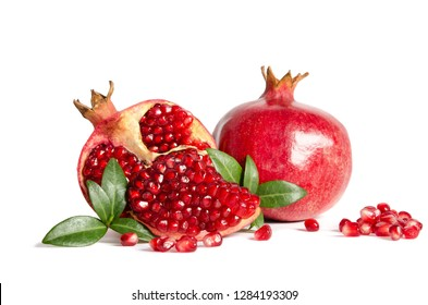 whole Pomegranate and parts of Pomegranate with leaves and seeds isolated on white