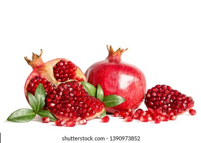 whole Pomegranates and three parts of Pomegranate with leaves and seeds isolated on white