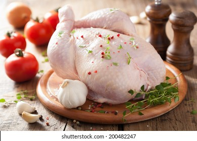 whole raw chicken with rose pepper and thyme