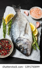 Whole raw Dorado fish with rosemary, lemon slices and seasonings on a black wooden background.Close-up
