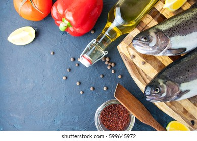 Whole raw salmon and fresh vegetables on a dark background