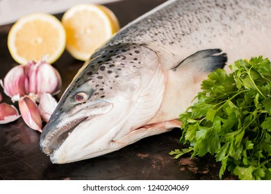 Whole raw salmon with parsley, garlic and lemon.