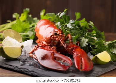 whole red lobster with ice on black slate plate