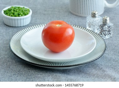 Whole red ripe organic tomato on black and white striped plate with chopped green chives in horizontal format.  Healthy eating concept.