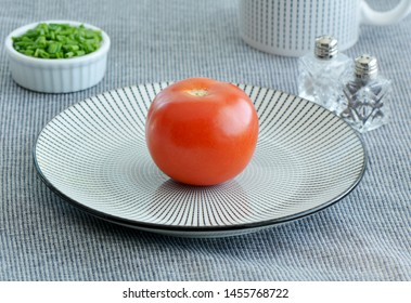 Whole red ripe organic tomato on black and white striped plate with chives in horizontal format.  Healthy eating concept.